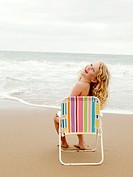 Young girl sitting on a beach chair at the beach