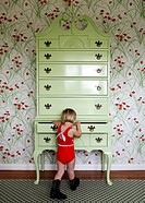 Girl rummaging in large dresser