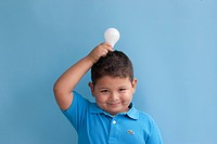 Boy in blue polo holding light bulb
