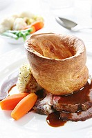 Beef cooked dinner with big yorkshire pudding and vegetables and gravy