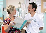 Hospital staff. Physiotherapist right talking to a discharge coordinator on a hospital ward.