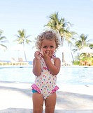 Toddler girl in bathing suit picking her nose