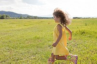 Young girl in yellow sundress running in field