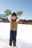 Young boy with branches for antlers