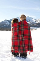 Boy and girl wrapped in red plaid blanket in the snow