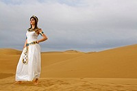 Girl dressed like Cleopatra posing on the desert dunes