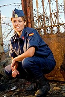 Military girl posing with a spike fence in background
