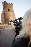 A woman making video film of the ruins of Aberystwyth castle to upload to a stock video clip website, Wales UK