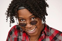 Young African-American woman looking over sunglasses posing for portrait