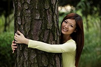 Chinese woman hugging a tree and smiling