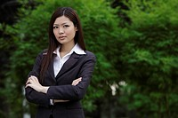 Chinese woman looking at camera with arms folder outside