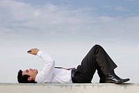 man in suit laying on ground looking at phone, smiling