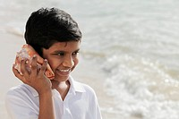 Young boy listening to sea shell