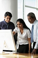 Indian woman looking at a computer with male colleagues