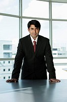 Indian businessman standing behind desk