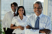 Three Indian business people smiling together