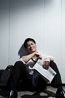 Chinese man sitting on ground holding newspaper and smiling