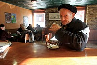 Elderly man takes a coffee in a bar while friends play cards in backgroudn. A Fonsagrada (Lugo)