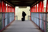 England, Shropshire, Telford, A businessman with luggage crossing the footbridge at Telford Central railway station.