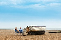 A couple relax on the beach in Aldeburgh , Suffolk , Uk