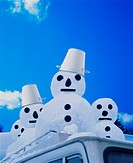 Four snowmen on the roof of a car