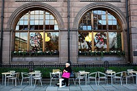 Scotland, Midlothian, Edinburgh, A woman relaxes outside a bar restaurant around Saint Andrew Square in the New Town of Edinburgh