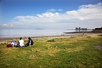 Scotland, City of Edinburgh, Edinburgh, Two people sitting on the grass looking out to sea at Granton Harbour in Edinburgh