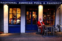 Scotland, City of Edinburgh, Edinburgh, A man in costume sits outside a pizza restaurant during the Edinburgh Christmas Santa Stroll