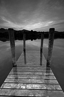 England, Cumbria, Keswick, Derwentwater jetty, partially submerged in the lake at dusk.