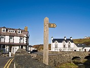 North Wales, Gwynedd, Aberdaron, Footpath sign and white washed houses by stone bridge over Afon Daron River.