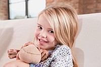 Germany, Cologne, Girl 4-5 with a stuffed toy, sitting on sofa (thumbnail)