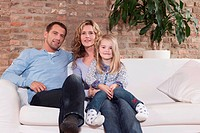 Germany, Cologne, Family sitting on sofa in living room, smiling, portrait