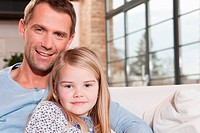 Germany, Cologne, Father and daughter 6_7 sitting on sofa, smiling, portrait, close_up