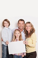 Germany, Cologne, Family holding blank carton, smiling, portrait