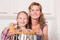 Germany, Cologne, Mother and daughter 6_7 cooking pasta, smiling, portrait