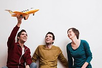 Men and women playing with toy aeroplane, smiling.