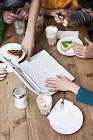 Friends using laptop, having breakfast
