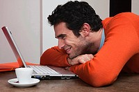 Man with coffee cup, smiling at laptop