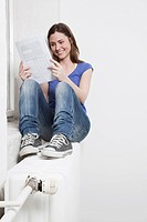 Woman holding document, smiling.