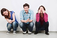 Men and women crouching, covering eyes, laughing