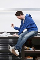 Man sitting on desk using laptop, gesturing