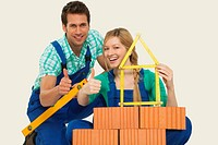 Man and woman behind stack of bricks holding tape measure and spirit level, portrait
