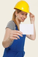 Woman wearing hard hat and holding blank paper, smiling, portrait