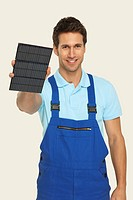 Man holding solar cell, smiling, portrait