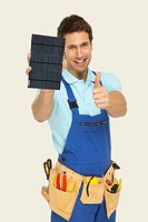 Man holding solar cell and showing thumbs up sign, portrait