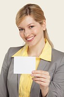 Businesswoman holding blank note, smiling