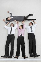 Four business people, businessmen and businesswoman lifting colleague, portrait, elevated view