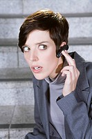 Germany, Bavaria, Munich, Business woman wearing bluetooth headset, portrait, close_up