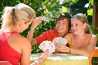 Austria, Salzburger Land, Teenagers 14_15 playing cards in garden