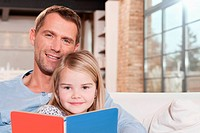 Germany, Cologne, Father and daughter 6_7 reading book on sofa, portrait, close_up